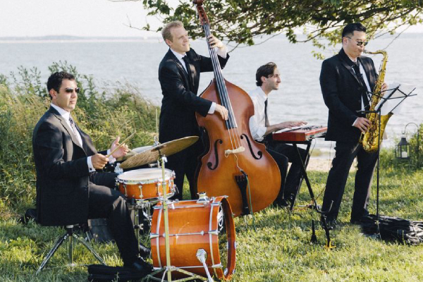 Image Showing The Quartet of Wedding Musicians Playing Their Instruments In An Outdoor Party.
