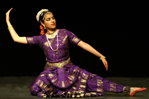 An Image of a girl performing a sitting pose in Bharatnatyam